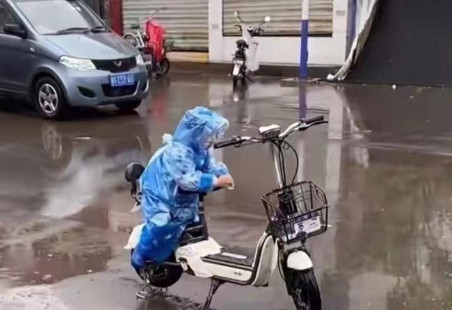 Ngồi trông xe cho mẹ giữa trời mưa, cậu bé có hành động bất ngờ làm bao người lớn tan chảy - Ảnh 2.