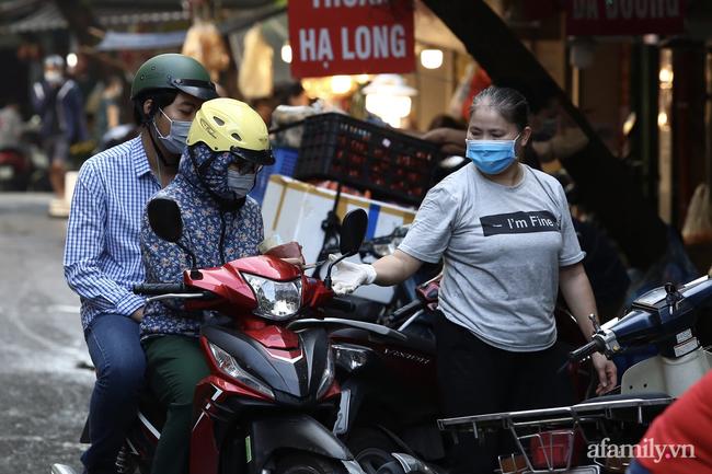 Buổi sáng đầu tiên cách ly toàn xã hội, đường phố Hà Nội vắng vẻ, người dân chỉ tập trung đông tại một số khu chợ để mua đồ ăn uống, sinh hoạt cho những ngày sắp tới - Ảnh 12.