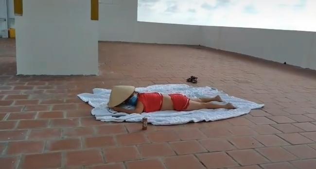 Người phụ nữ nghi là F0 ăn mặc hớ hênh lên sân thượng nằm phơi nắng, bị nhắc nhở vẫn tỉnh bơ như không - Ảnh 2.