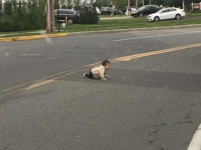 Hoảng hồn với hình ảnh bé trai bò ngang qua đường quốc lộ, xung quanh không hề có cha mẹ hay người thân nào - Ảnh 1.