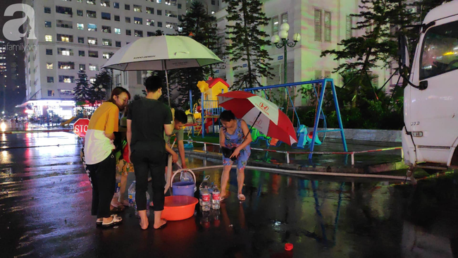 Chùm ảnh người dân đội mưa đi lấy nước tại khu chung cư Linh Đàm - Ảnh 4.