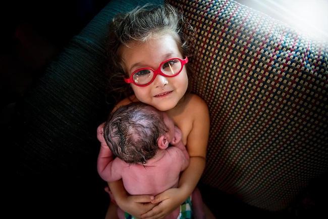 Bức ảnh ngọt lịm tim cô chị 3 tuổi da tiếp da với em trai mới sinh - Ảnh 2.