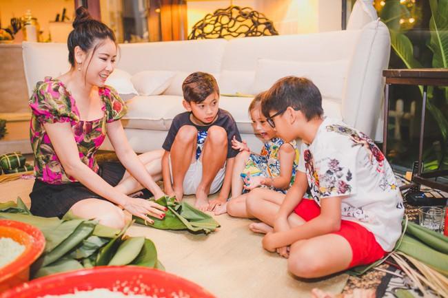 Các con Hà Kiều Anh chăm chú xem mẹ gói bánh chưng ngày Tết - Ảnh 4.