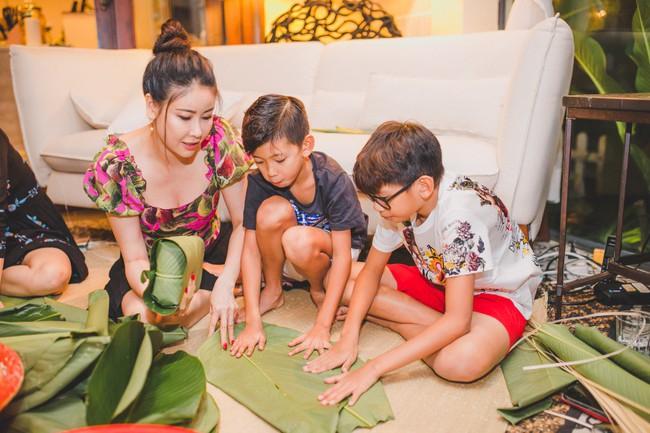 Các con Hà Kiều Anh chăm chú xem mẹ gói bánh chưng ngày Tết - Ảnh 7.