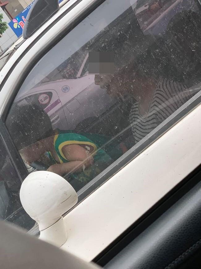 Mẹ để con trai ôm vô lăng ô tô đang lưu thông trên đường, bức ảnh chụp gây phẫn nộ - Ảnh 1.