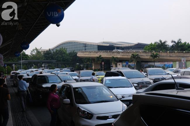 Sân bay Tân Sơn Nhất đông nghẹt: Trẻ em ngủ gục, người lớn cầm sẵn hoa chờ đón Việt kiều về nước ăn Tết - Ảnh 1.