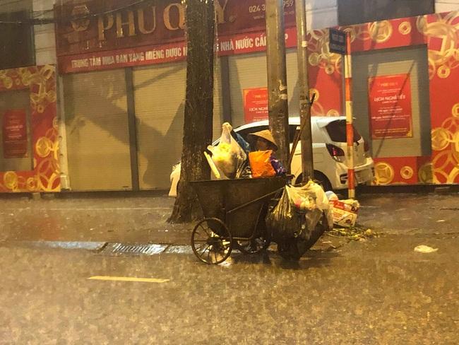 Chạnh lòng với hình ảnh cô lao công dọn rác bên lề đường trong đêm 30 Tết mưa bão - Ảnh 2.