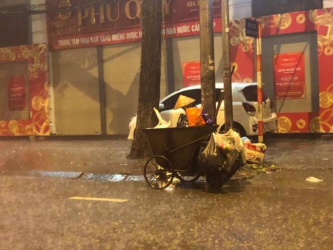 Chạnh lòng với hình ảnh cô lao công dọn rác bên lề đường trong đêm 30 Tết mưa bão - Ảnh 3.