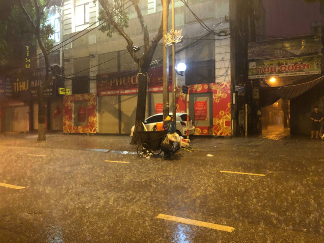 Chạnh lòng với hình ảnh cô lao công dọn rác bên lề đường trong đêm 30 Tết mưa bão - Ảnh 4.