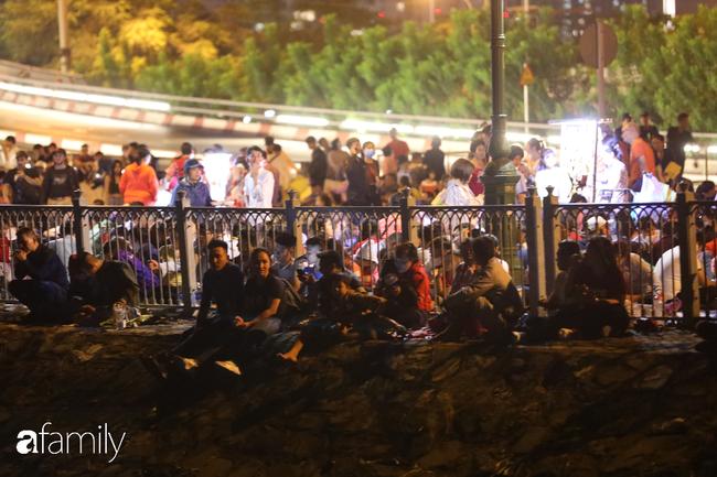 """Khác hẳn với sự vắng vẻ của Hà Nội, người Sài Gòn ngồi xếp lớp như """"cá mòi"""" để có được chỗ tốt xem pháo hoa đêm giao thừa - Ảnh 4."""