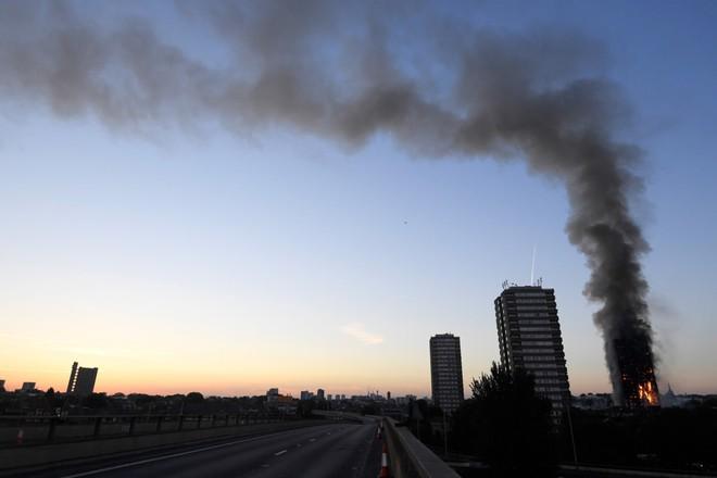 Hình ảnh tòa nhà 27 tầng trơ trụi, đen thui sau khi ngọn lửa được kiểm soát - Ảnh 1.