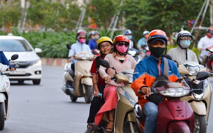 Ảnh: Người dân Hà Nội mặc áo khoác, co ro trong cái rét cuối thu chạy xe máy về nhà sau giờ làm